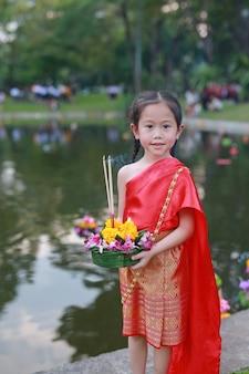Ragazza asiatica in vestito tradizionale tailandese con krathong per perdono goddess gange.