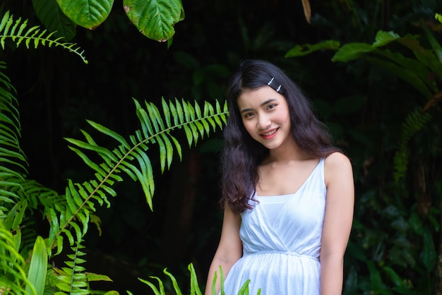 I turisti asiatici della ragazza visitano la bellezza della natura nel segno del parco nazionale della cascata di phlio a chanthaburi, tailandia.