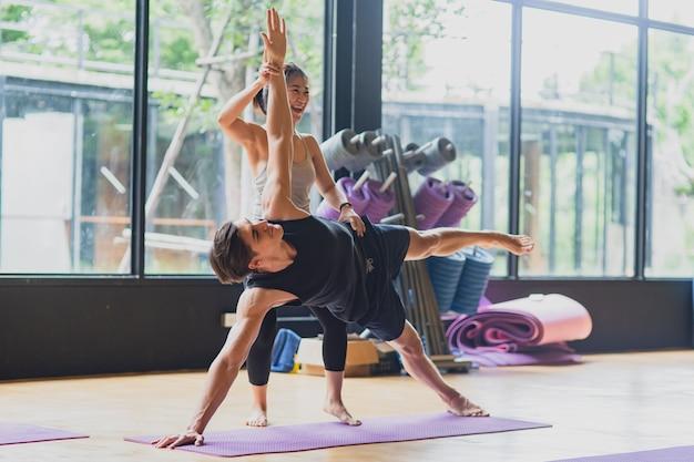 La ragazza asiatica che si prepara e insegna al suo ragazzo a correggere la posa di yoga