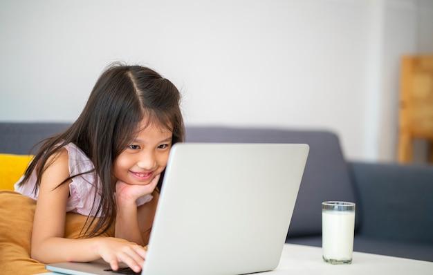Ragazza asiatica utilizzando laptop per studio online durante l'istruzione domestica a casa. homeschooling, studio online, nuovo normale, apprendimento online, virus corona o concetto di tecnologia educativa