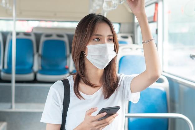 Ragazza asiatica che indossa la maschera mentre usa lo smartphone sull'autobus