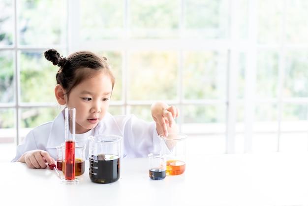 Ragazza asiatica che indossa un'uniforme da scienziato bianco l'apprendimento ha condotto un esperimento scientifico