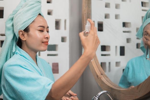 La ragazza asiatica indossa un asciugamano mentre si spruzza la crema idratante per la pelle del viso davanti allo specchio