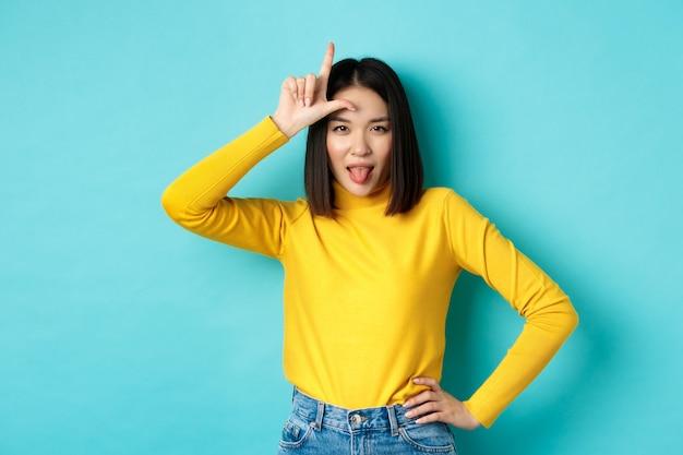 Vincitore della ragazza asiatica che deride la squadra persa, mostrando il segno del perdente sulla fronte e attaccando la lingua ignorante