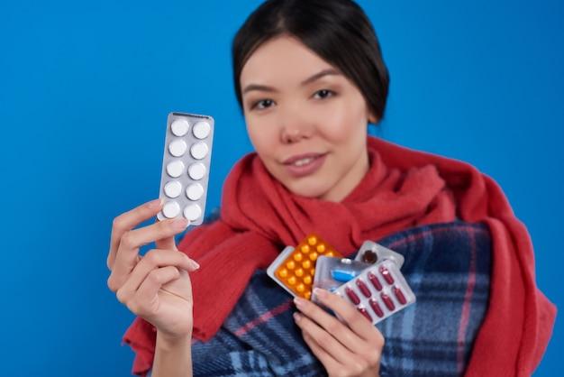 Ragazza asiatica con le pillole di presa fredde isolate.
