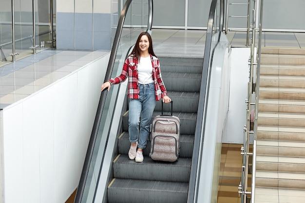 Ragazza asiatica con la valigia giù per la scala mobile in aeroporto.
