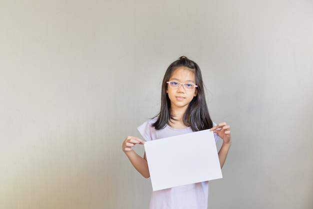 Ragazza asiatica con foglio di carta bianco, ragazza con carta bianca vuota, mock up segno in bianco per concetti di design creativo messaggio.