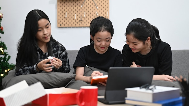 Ragazze asiatiche che hanno lezione online a casa insieme.