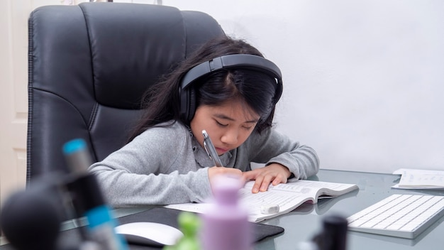 Le ragazze asiatiche studiano online con i laptop. i bambini indossano le cuffie per la digitazione del taccuino della tastiera che imparano utilizzando lezioni su internet in quarantena. gli studenti imparano con la lezione online su internet dalla scuola covid-19