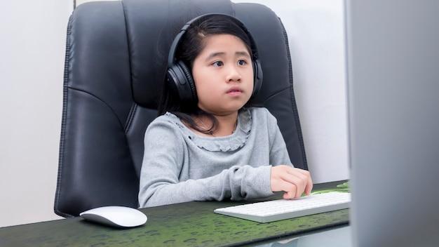 Le ragazze asiatiche studiano online con i computer portatili i bambini indossano le cuffie per digitare sulla tastiera l'apprendimento del taccuino