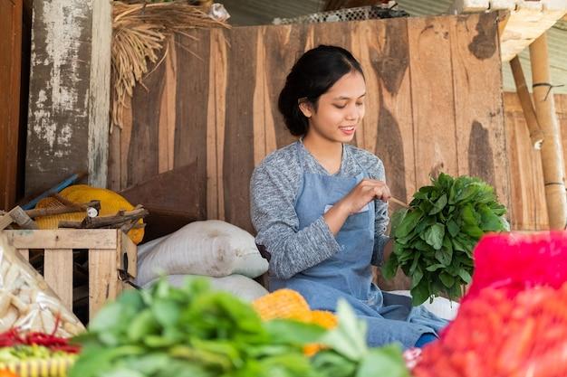 Donna asiatica del fruttivendolo seduto tenendo gli spinaci per legare nella bancarella di verdure