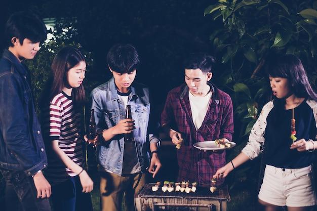 Il gruppo asiatico di amici che hanno barbecue all'aperto del giardino che ride con la birra alcolica beve sulla notte