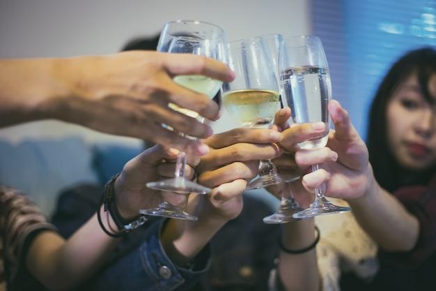 Gruppo asiatico di amici che hanno festa con bevande alcoliche e giovani che godono in un bar