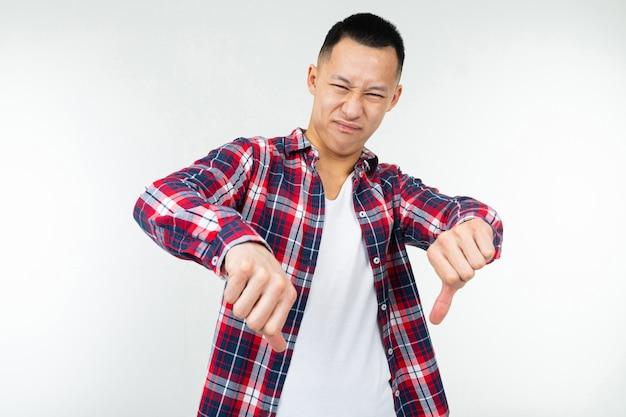 Il tipo asiatico in una camicia a quadretti spalancata mostra il dito di avversione giù su uno studio bianco isolato