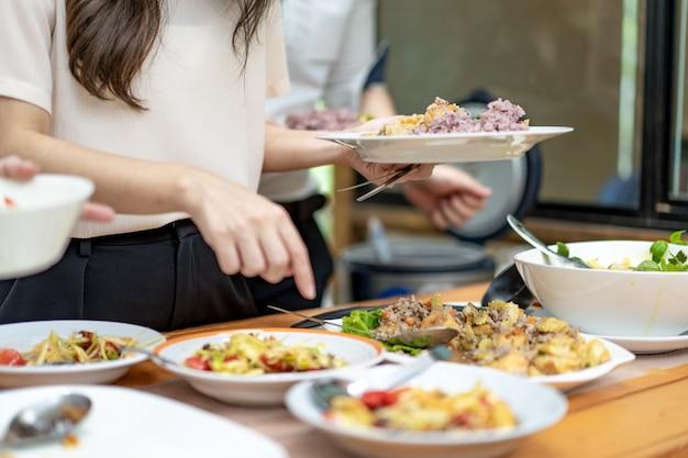 Il ragazzo asiatico (vicino alle mani) sta raccogliendo il cibo tailandese tradizionale; somtum, omelette, zuppa thailandese, ecc. sul bancone di legno.