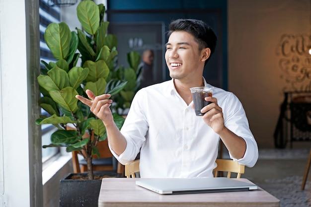 Uomo d'affari asiatico bello o impiegato che lavora alla caffetteria