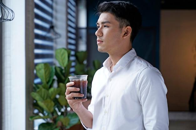 Uomo d'affari asiatico bello o impiegato o giovane studente che beve caffè al negozio di caffè