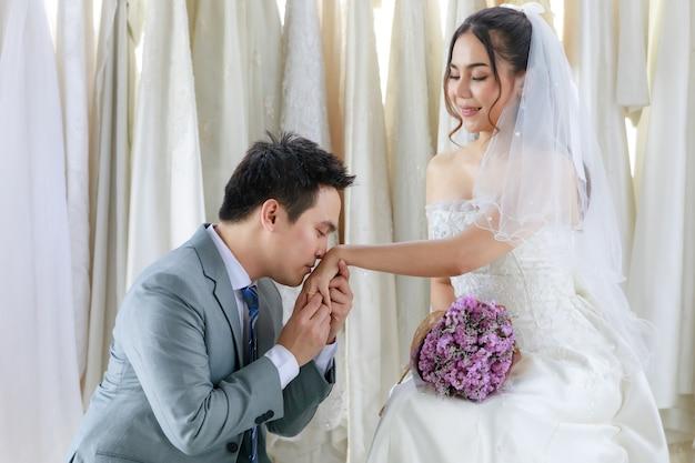 Sposo asiatico bello in abito formale grigio inginocchiato baciando la mano sinistra con anello di gioielli in oro rosa con diamanti sulla mano della sposa felice in abito da sposa bianco con bouquet di fiori viola nello spogliatoio.