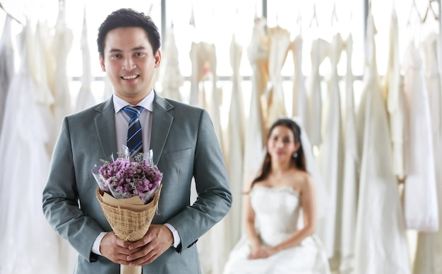 Bello sposo asiatico in abito formale grigio con cravatta in piedi guarda la macchina fotografica con bouquet e bella sposa felice in abito da sposa lungo bianco in sfocatura dello sfondo.