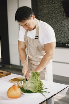 Uomo bello asiatico che cucina a casa.