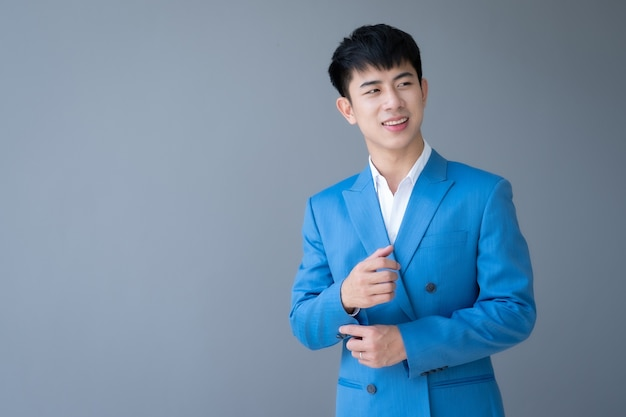 Uomo bello asiatico sul muro grigio