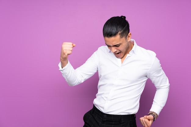 Uomo bello asiatico isolato su sfondo blu che celebra una vittoria