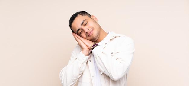 Uomo bello asiatico che fa gesto di sonno nell'espressione dorable