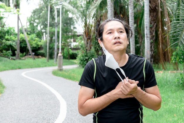 Un bell'uomo asiatico si toglie una maschera perché è stanco e soffoca per aver indossato una maschera