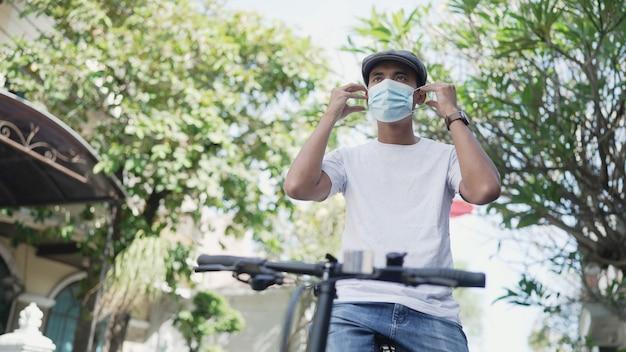 Un bell'uomo asiatico indossa una maschera mentre va in bicicletta