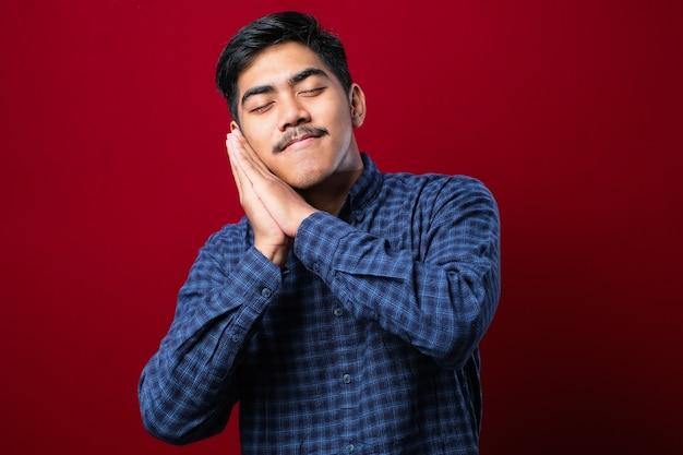 Un bell'uomo asiatico che indossa una camicia che dorme stanco sogna e posa con le mani insieme mentre sorride con gli occhi chiusi su sfondo rosso
