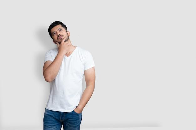 Uomo bello asiatico sulla maglietta bianca che ha dubbi mentre cerca su sfondo bianco isolato
