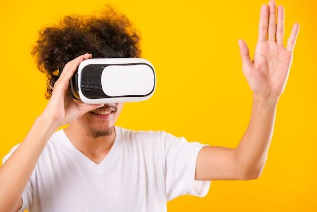 Bell'uomo asiatico con i capelli ricci che utilizza l'auricolare per realtà virtuale o il vetro vr