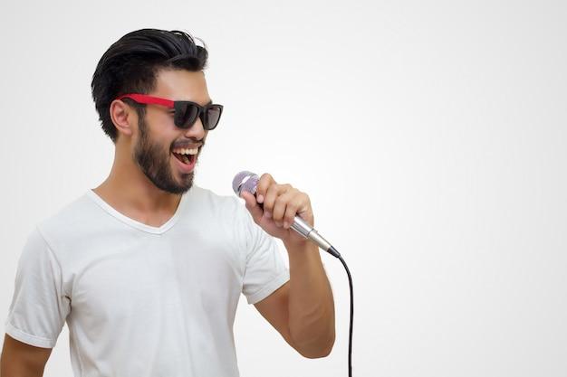 Uomo bello asiatico con i baffi, sorridenti e cantanti al microfono isolato sul backgrou bianco