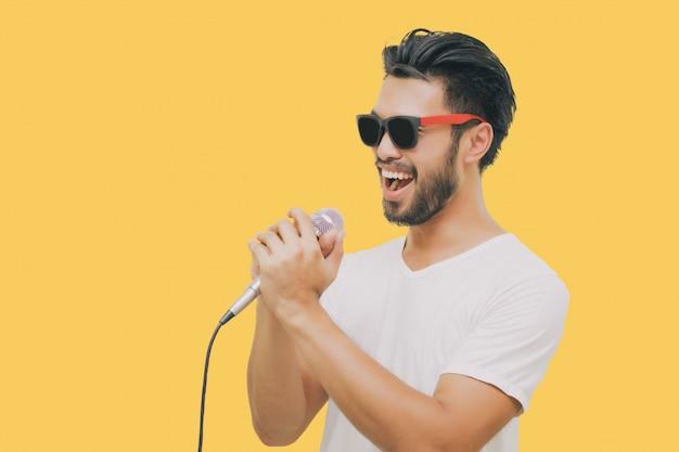 Uomo bello asiatico con i baffi, sorridente e cantando al microfono isolato su sfondo giallo