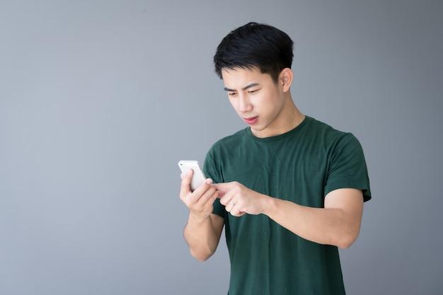 Giovane bello asiatico che tiene smartphone