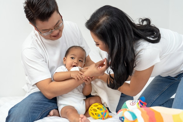 Scena asiatica della famiglia di felicità del bambino del ragazzo con il padre e madre nella camera da letto della casa