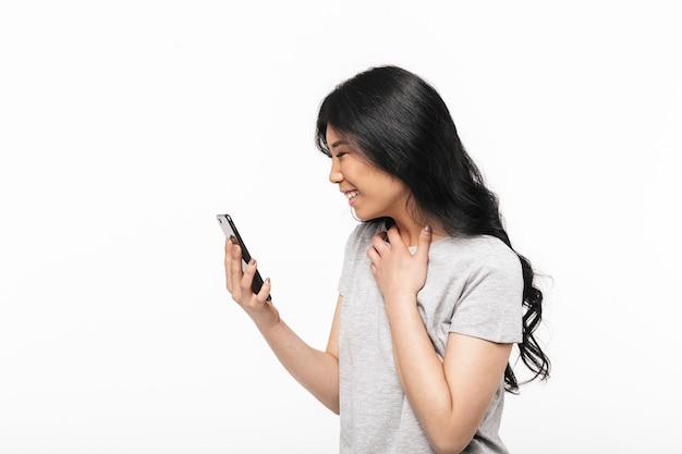 Asian felice bella giovane donna in posa isolato sul muro bianco utilizzando il telefono cellulare.