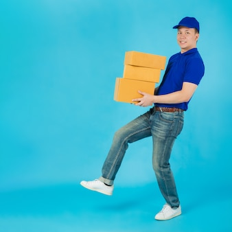 Uomo di consegna felice asiatico che trasportano cassette dei pacchi di carta isolate sulla parete di colore blu