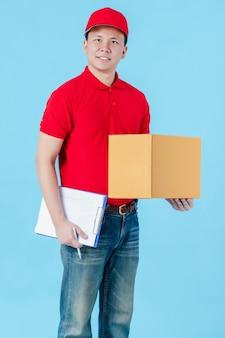 Fattorino asiatico felice che indossa una camicia rossa in piedi mentre tiene in mano scatole di pacchi di carta.