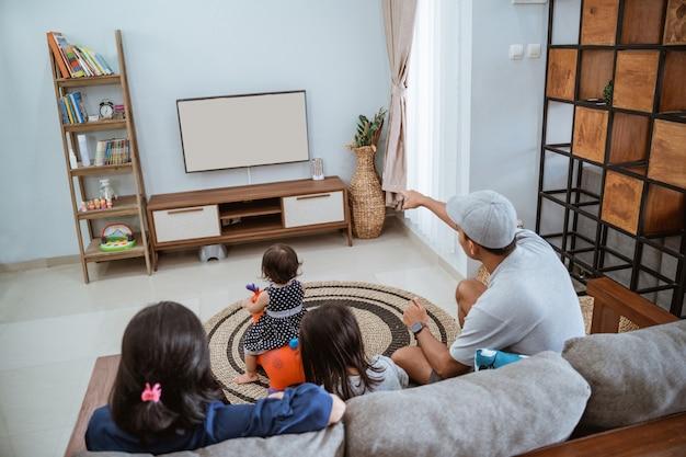Famiglia felice asiatica che si siede sul divano a casa a guardare la tv insieme