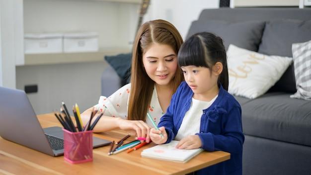 La mamma e la figlia felici asiatiche stanno usando il laptop per studiare in linea via internet a casa. concetto di e-learning durante il periodo di quarantena.