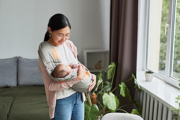 Madre asiatica felice che tiene in braccio il suo bambino e lo culla mentre cammina per la stanza