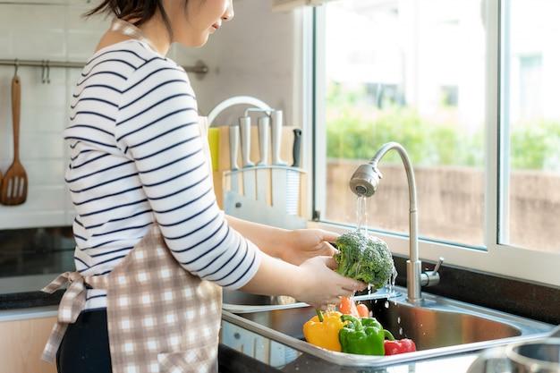 Donna in buona salute asiatica che lava i broccoli e l'altra verdura sopra il lavandino di cucina