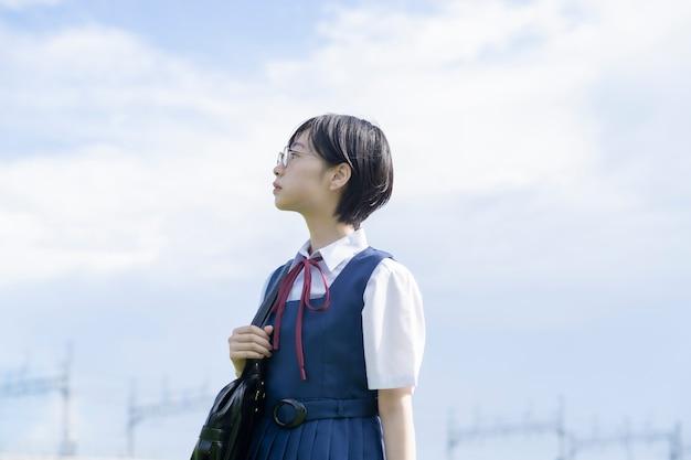 Ragazza asiatica della high school con i vetri che guardano in su al cielo