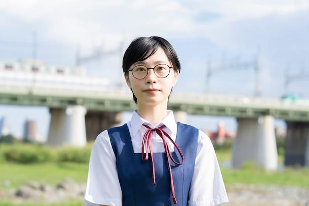 Ragazza asiatica del liceo con i capelli neri corti con gli occhiali