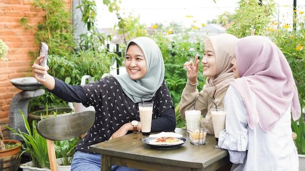 Selfie di gruppo donna asiatica hijab nella caffetteria con un amico