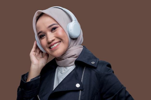 Hijab asiatico donna che indossa le cuffie wireless con un sorriso guardando la telecamera