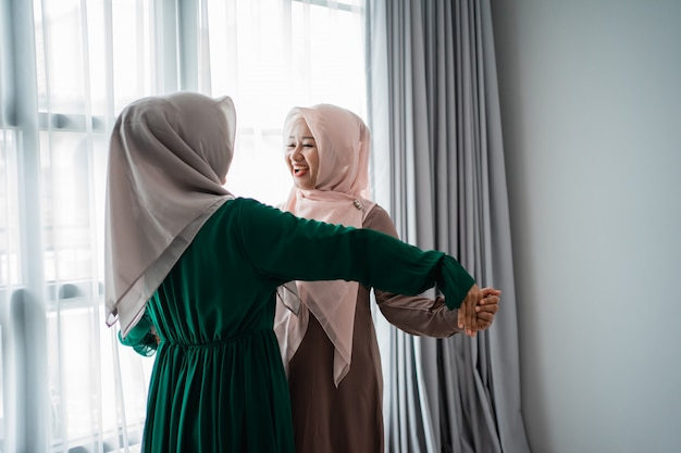 Le giovani donne asiatiche hijab sono felici di incontrare la loro amica