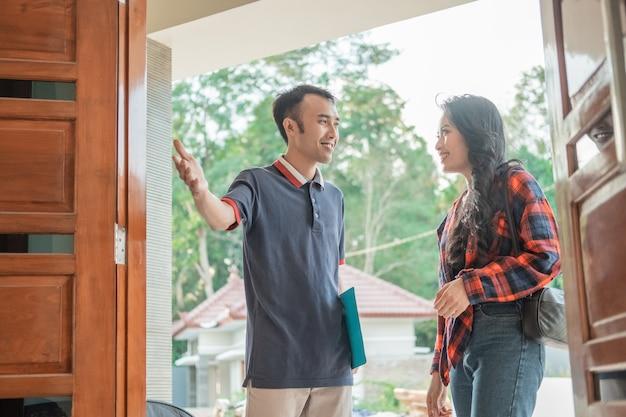 Il promotore di alloggi asiatico con un gesto della mano invita la bella donna ad entrare nella nuova casa mentre sta alla porta