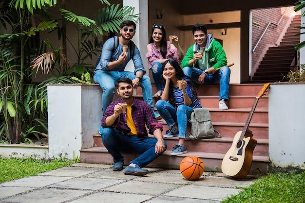Gruppo indiano asiatico di studenti universitari che bevono tè e caffè insieme in pausa nei locali del campus all'aperto. fare due chiacchiere